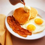Pancakes with eggs and bacon with syrup being poured