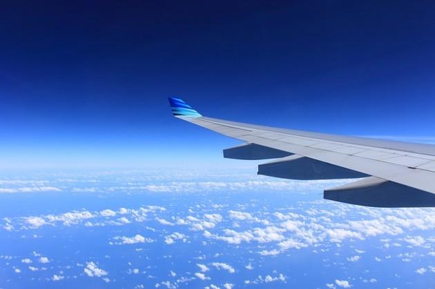Imagem da asa de um avião em alto céu.